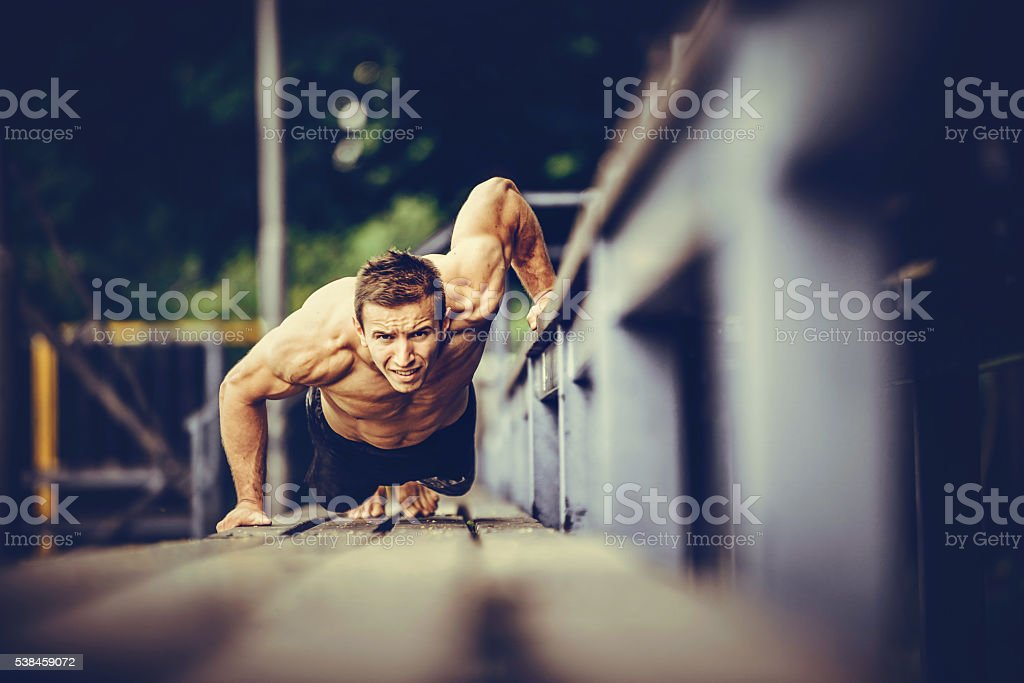 Young muscular man working out on public playground