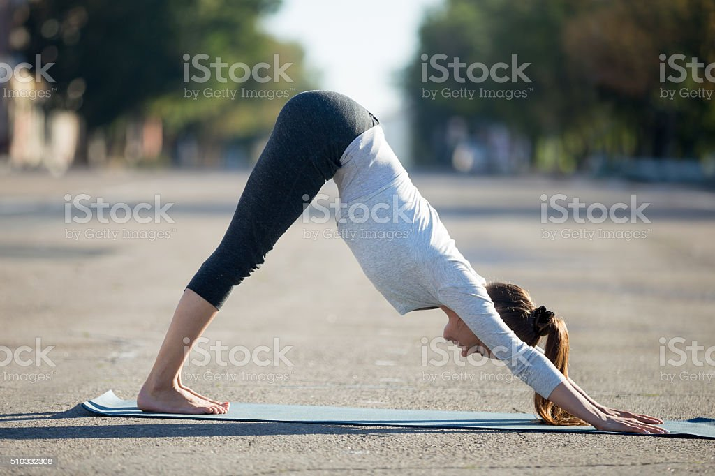 Street yoga: Downward facing dog pose stock photo