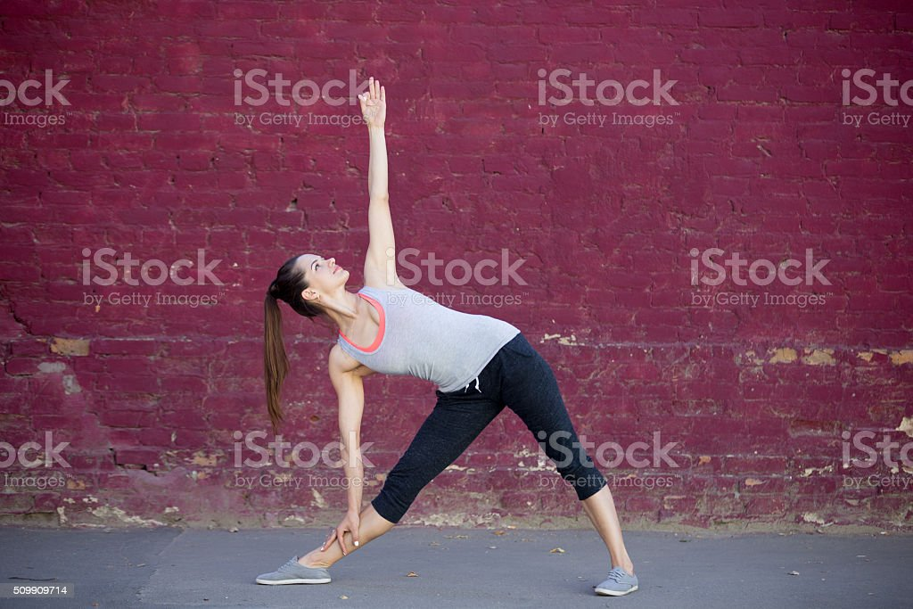 Street yoga: Utthita Trikonasana Pose stock photo