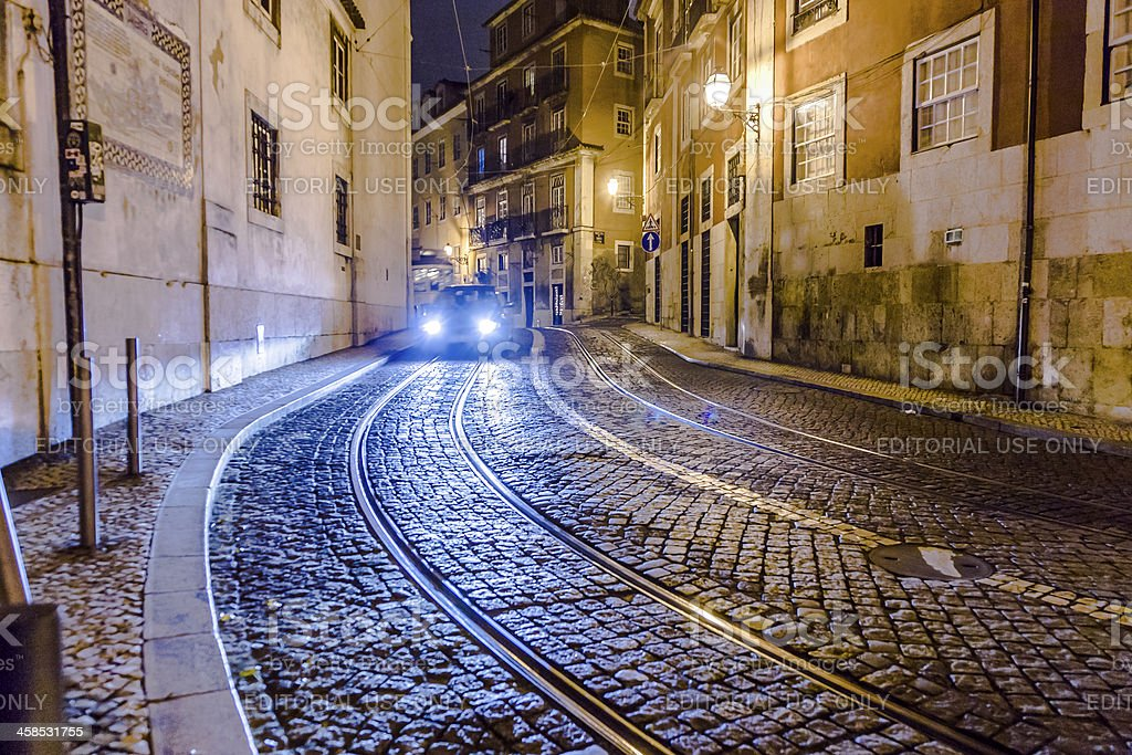 streetcar rails in the old part of Lisbon by night royalty-free stock photo