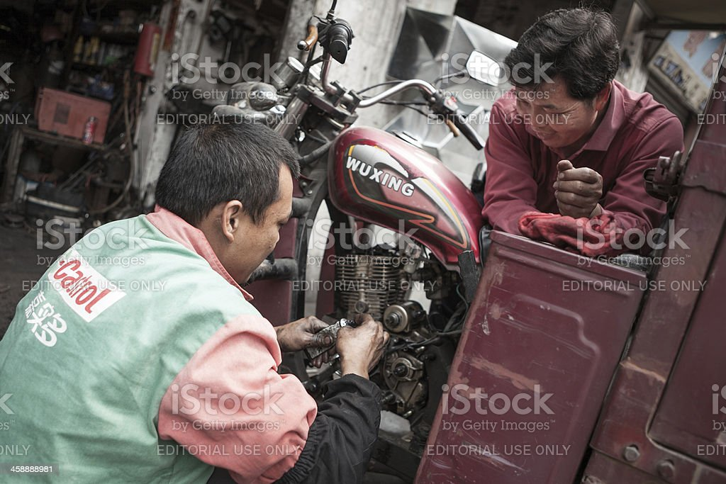 Streetview of garage mechanic working on motorcycle in China stock photo