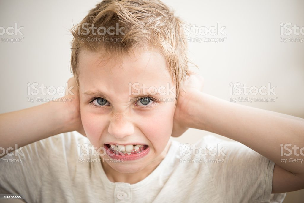 Stress and noise. The little boy closed his ears stock photo