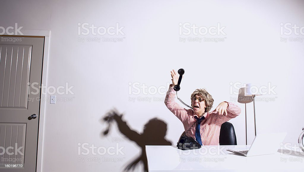 Stressed and Overworked Nerdy Businessman Tied Up With Telephone royalty-free stock photo