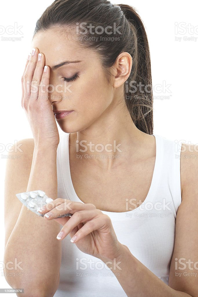 stressed and sad brunette holds some pills, isolated on white royalty-free stock photo