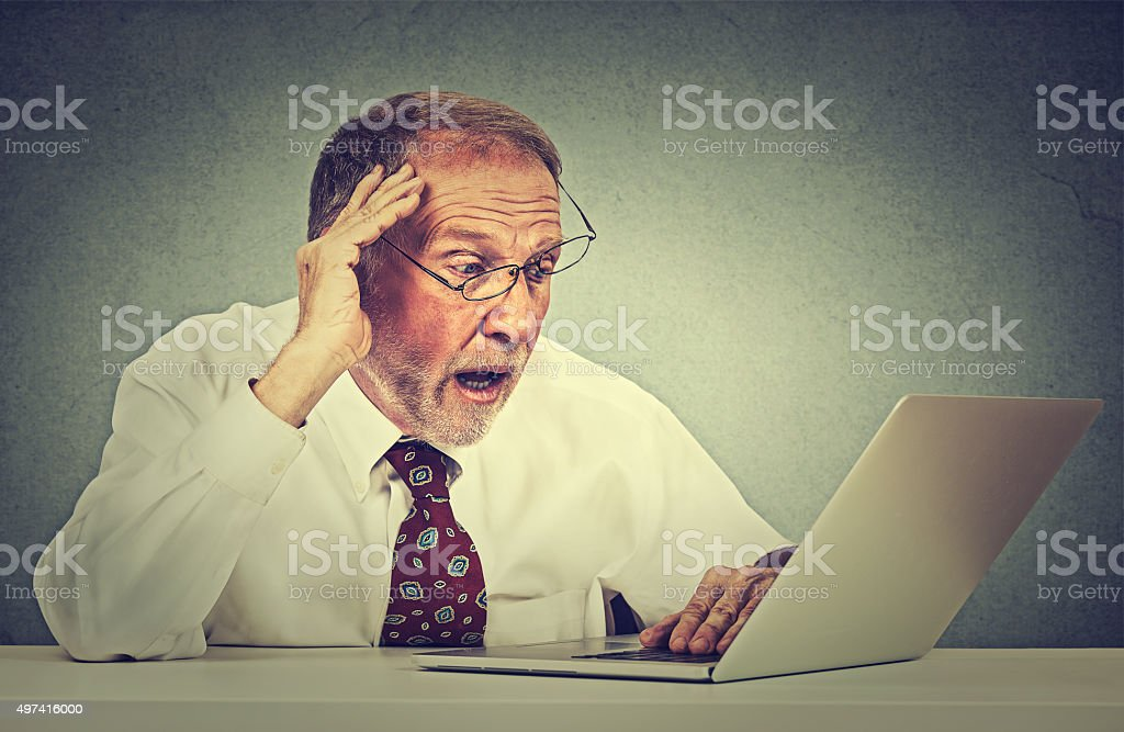 Stressed anxious senior man looking at laptop seeing bad news stock photo