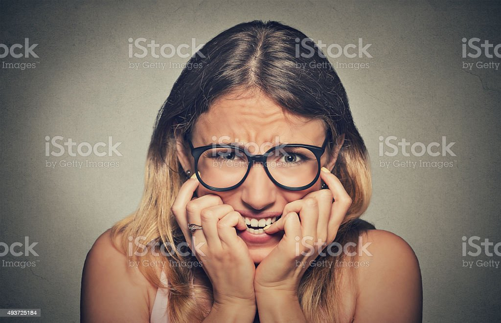 stressed anxious woman in glasses biting fingernails stock photo