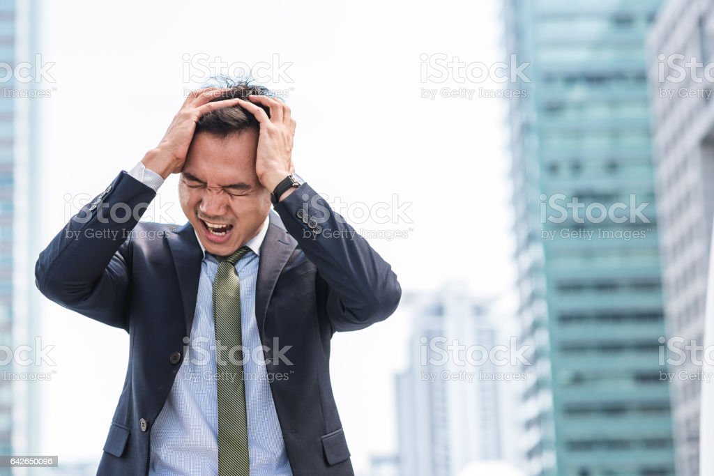 Stressed Asian businessman scream while cover his head stock photo