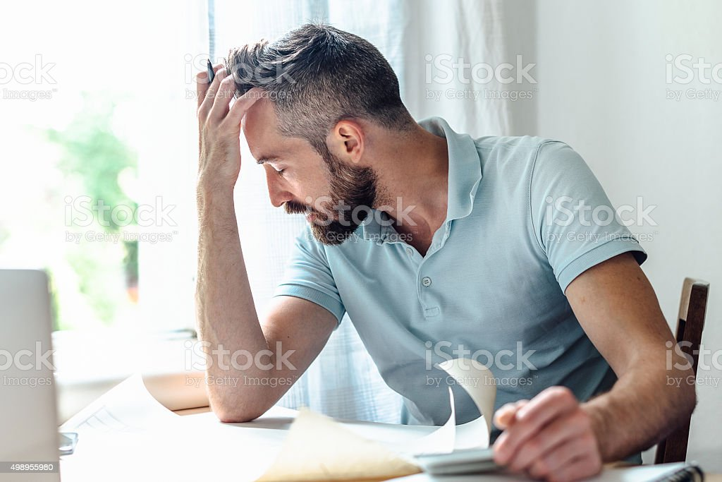 stressed bearded creative men holding head in head at desk stock photo