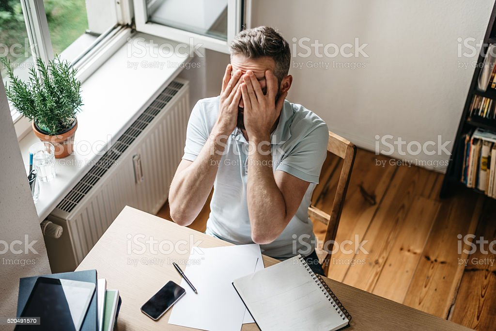 stressed bearded studying men holding head in head at desk stock photo