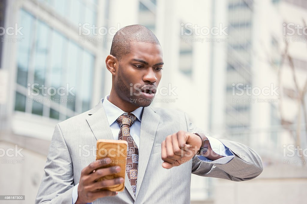 Stressed business man looking at wrist watch running late stock photo