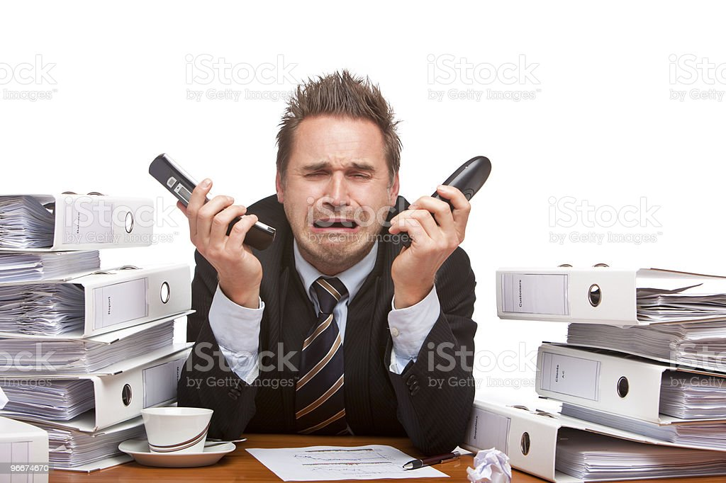 Stressed business man with telephones cries frustrated in office stock photo