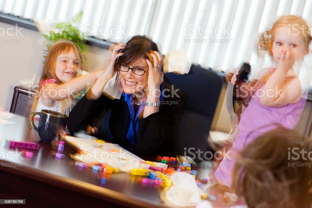Stressed Business Woman Working with Children in Office stock photo