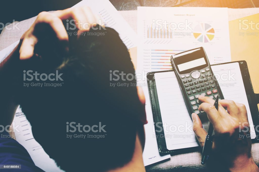 Stressed businessman and graph doing finance with calculate about cost. stock photo
