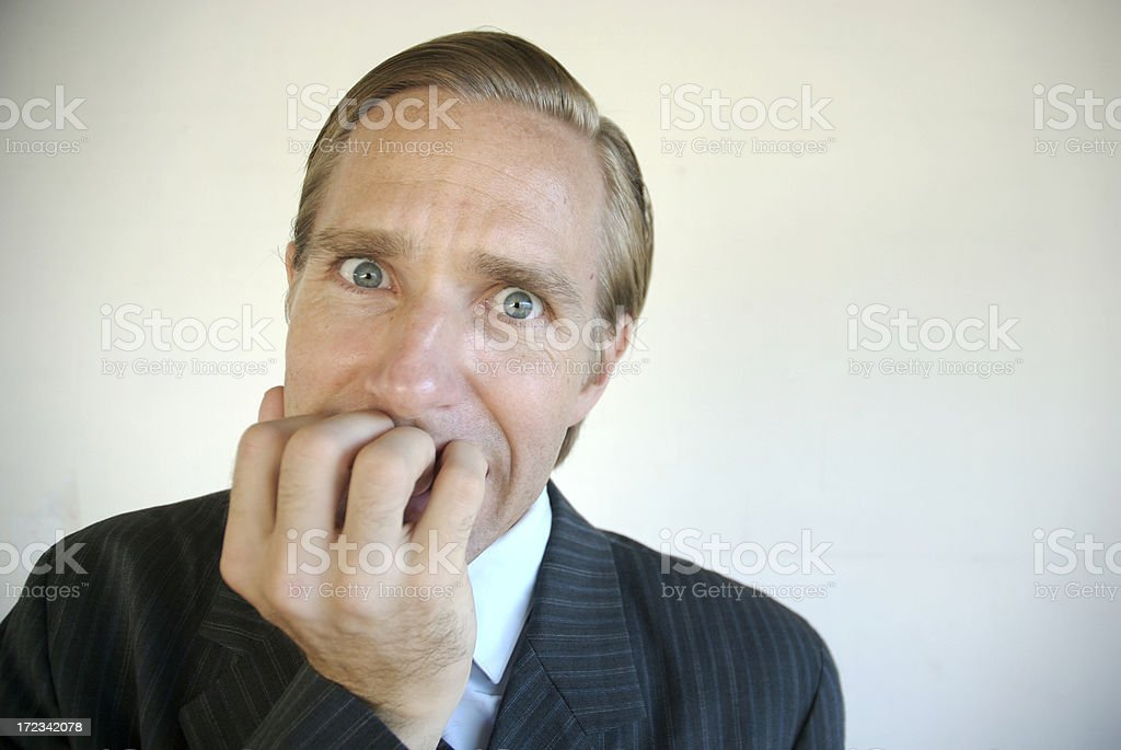 Stressed Businessman Chewing Fingers Looking at Camera royalty-free stock photo