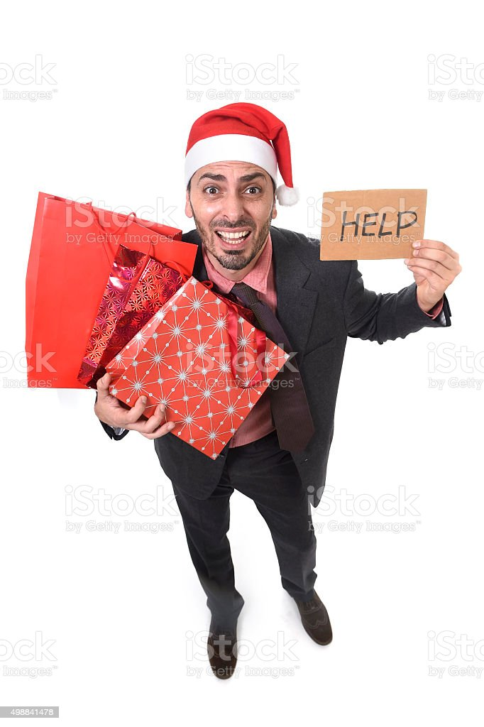 stressed businessman in Santa Claus hat holding shopping bags stock photo