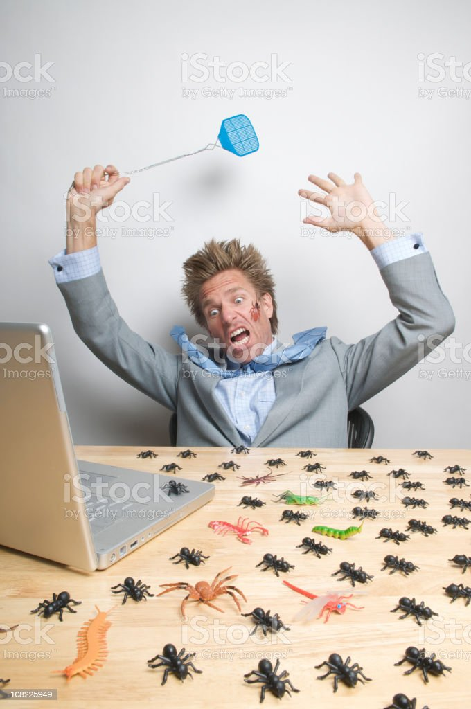 Stressed Businessman Is Attacked By Computer Bugs on Laptop royalty-free stock photo