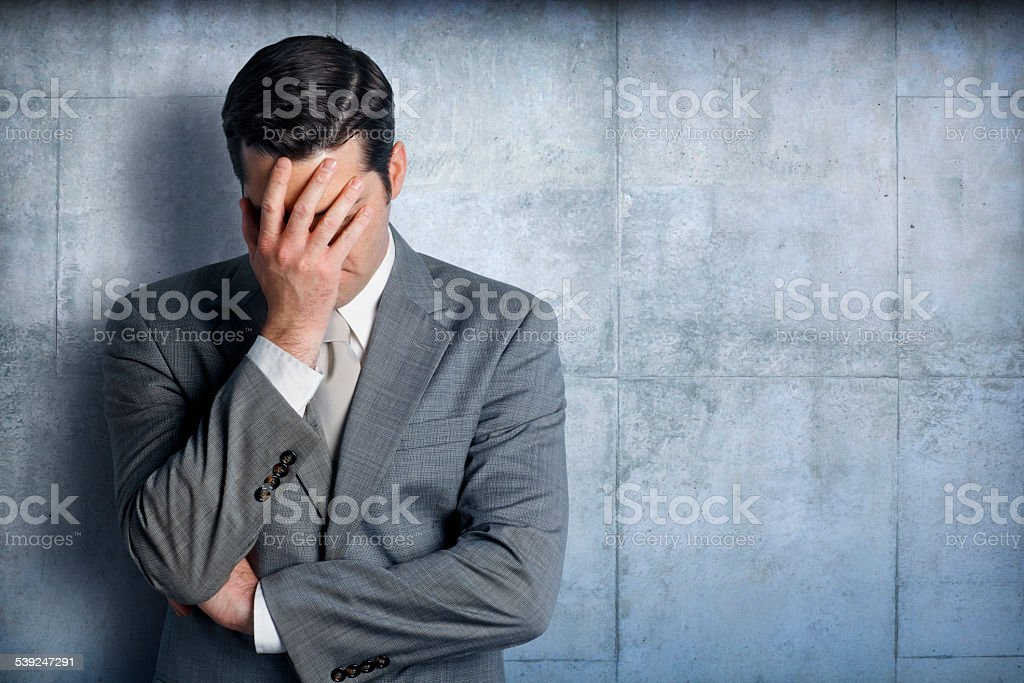 Stressed businessman leaning against concrete wall stock photo