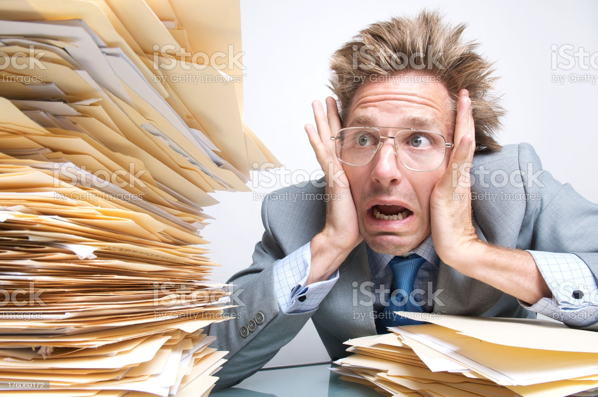Stressed Businessman Office Worker Freaking Out Next to Paperwork Pile royalty-free stock photo