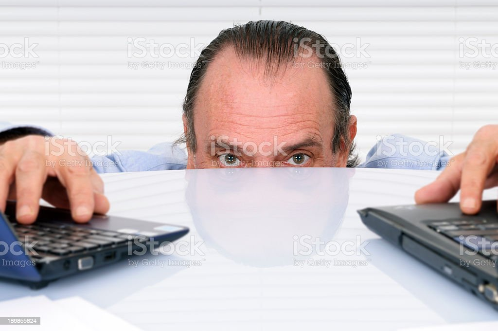 Stressed Businessman Peeking From The Desk royalty-free stock photo