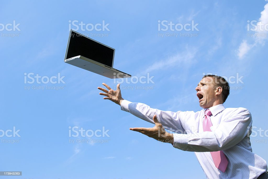 Stressed Businessman Reaches Out for his Flying Laptop Blue Sky royalty-free stock photo