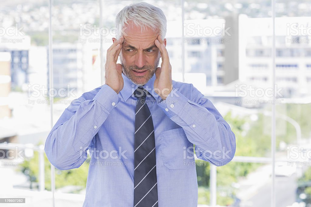 Stressed businessman rubbing his temples royalty-free stock photo