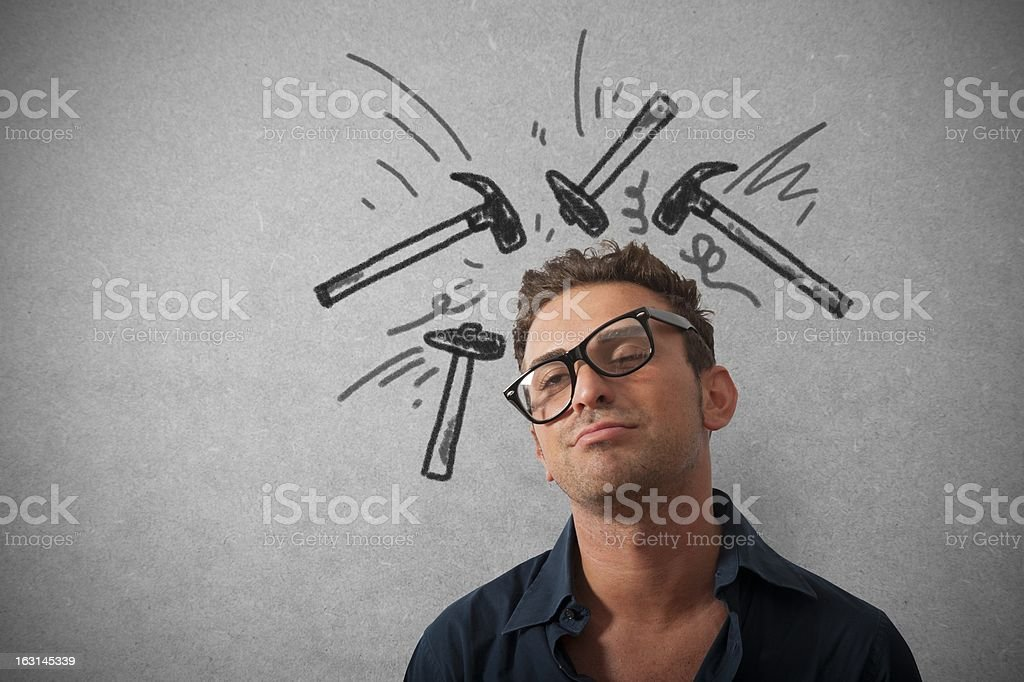A stressed businessman with crooked glasses and hammers stock photo