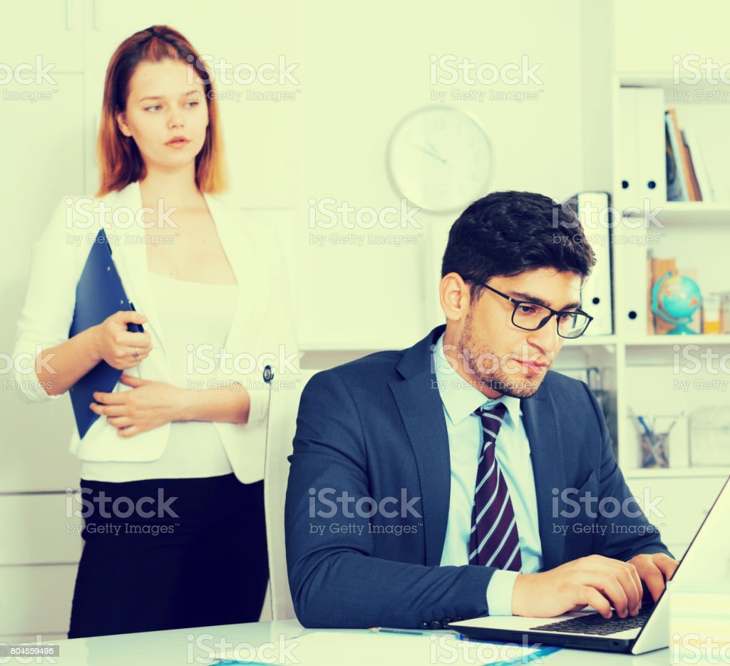 Stressed businessman with dissatisfied female colleague stock photo