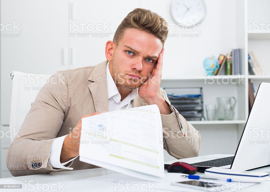 Stressed businessman with documents in office stock photo