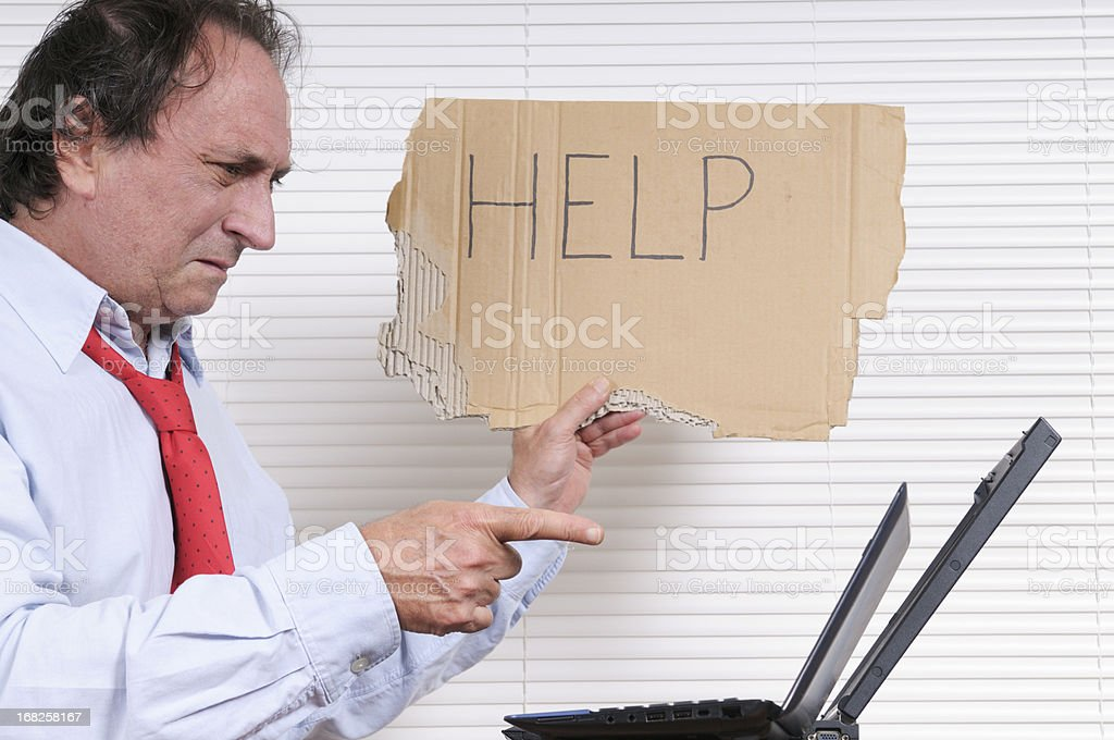 Stressed Businessman with Help Sign Looking PC royalty-free stock photo