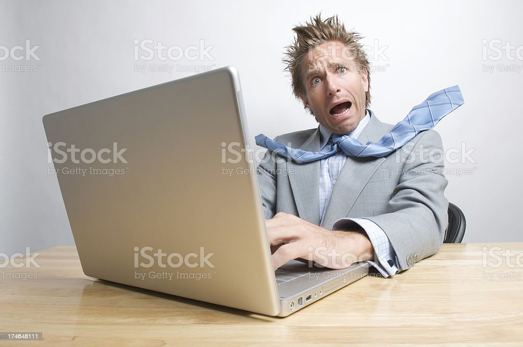 Stressed Businessman Working on Laptop Computer at Desk royalty-free stock photo