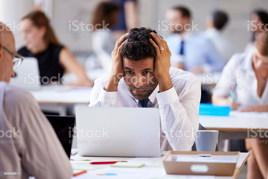 Stressed Businessman Working On Laptop In Busy Office stock photo