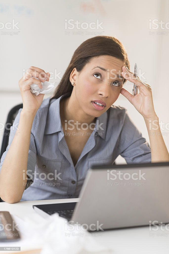 Stressed Businesswoman Holding Paper Ball And Pen At Desk royalty-free stock photo