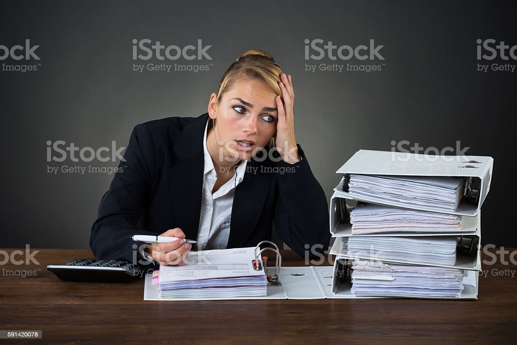 Stressed Businesswoman Looking At Folders While Working At Desk stock photo