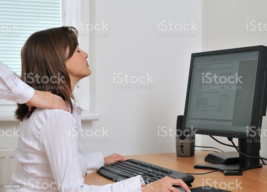 Stressed businesswoman working while receiving a massage royalty-free stock photo