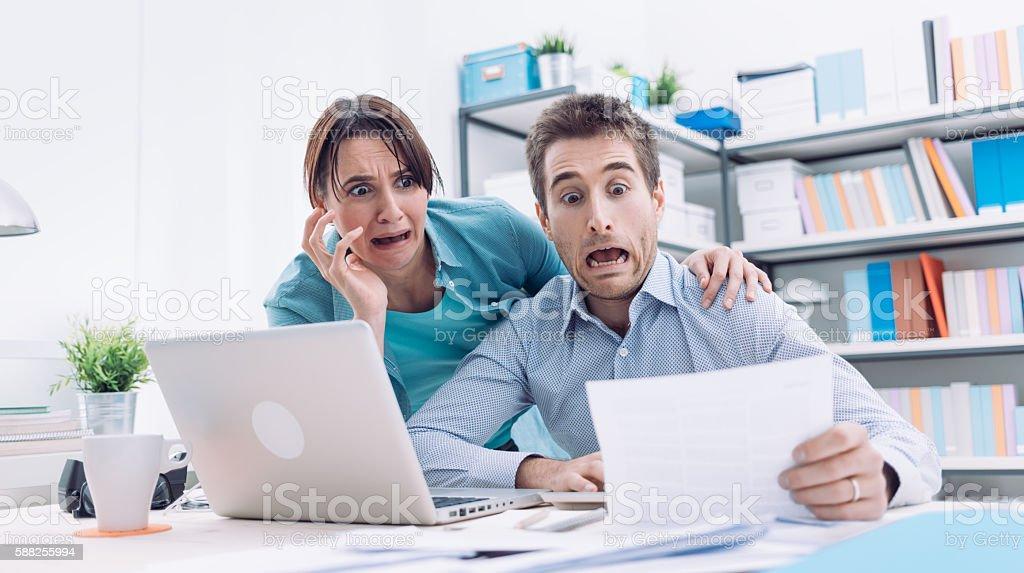 Stressed couple checking bills stock photo