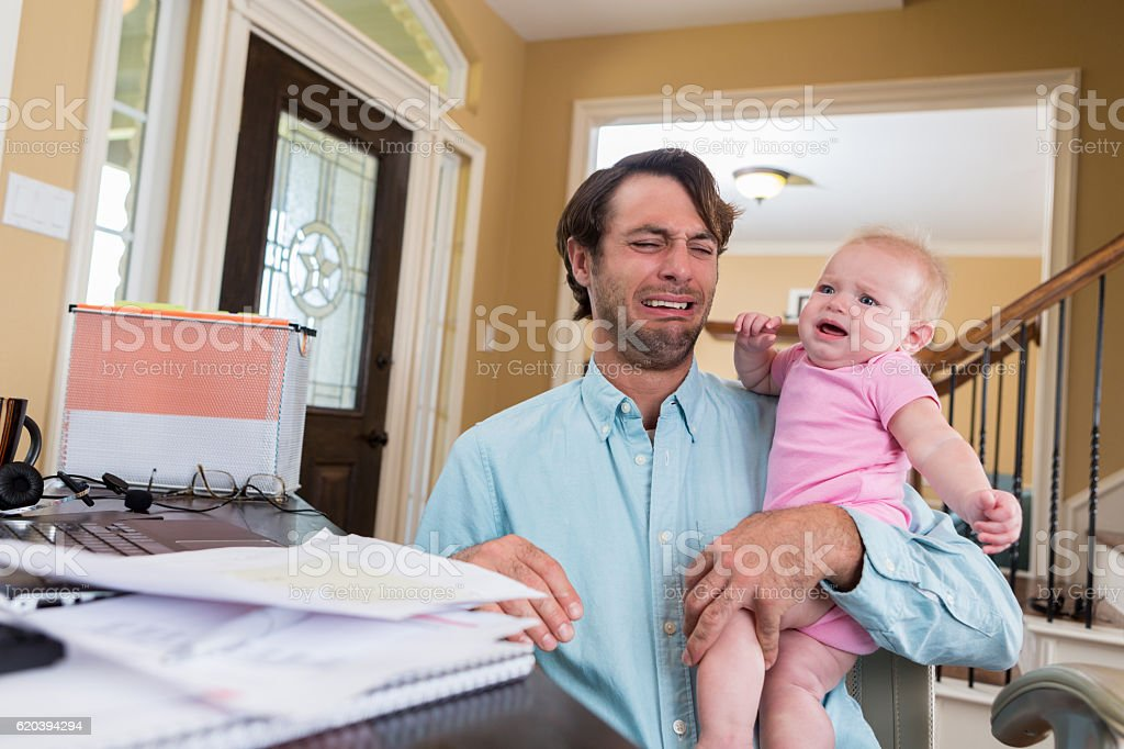 Stressed dad with baby working from home stock photo