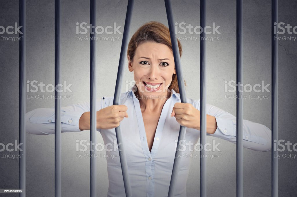 Stressed desperate angry businesswoman bending bars of her prison cell stock photo