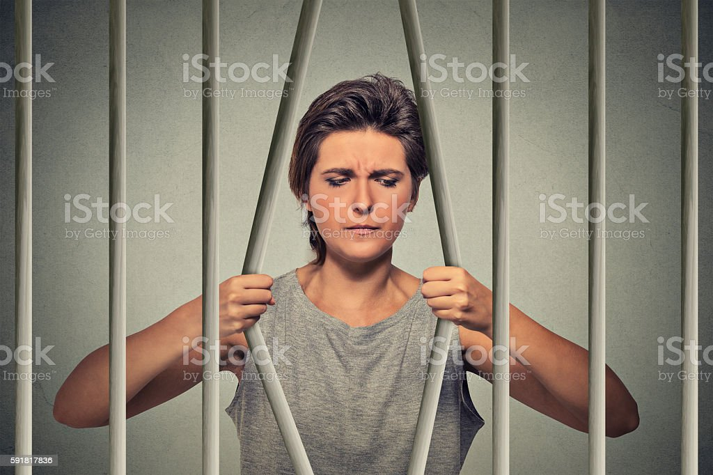 Stressed desperate woman bending bars of prison cell stock photo