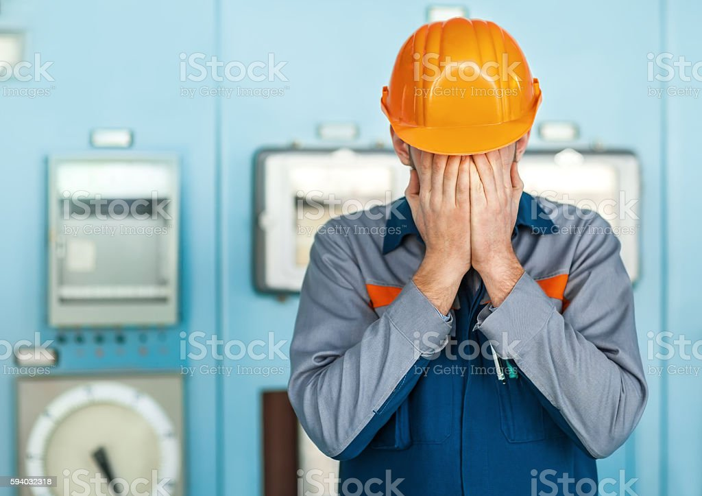 stressed engineer closed face by two hands stock photo