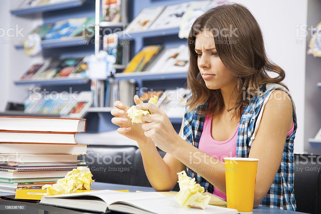 Stressed female student in a library royalty-free stock photo