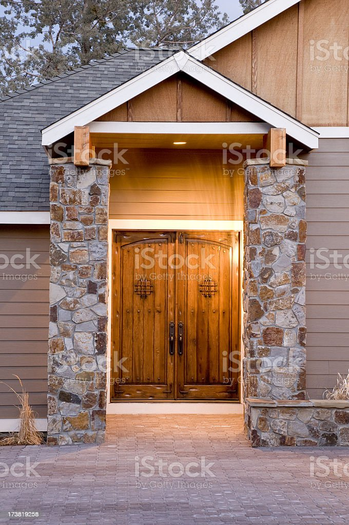 Stressed front doors with stone pillars royalty-free stock photo