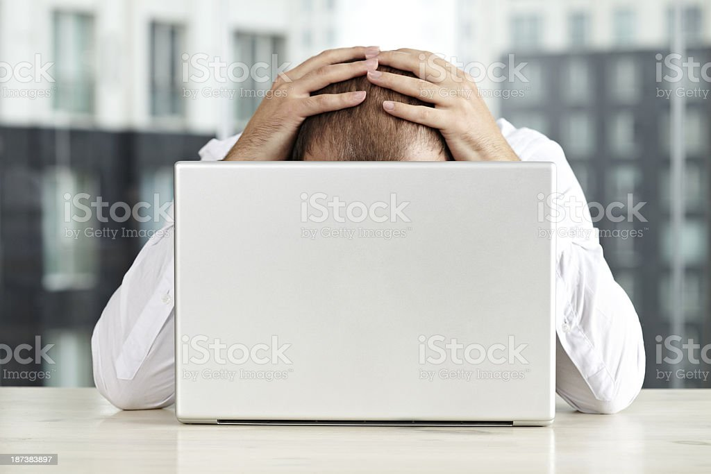 A stressed individual holding his head in his hands royalty-free stock photo