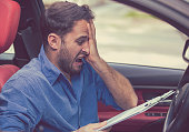 Stressed man driver with papers sitting inside his car