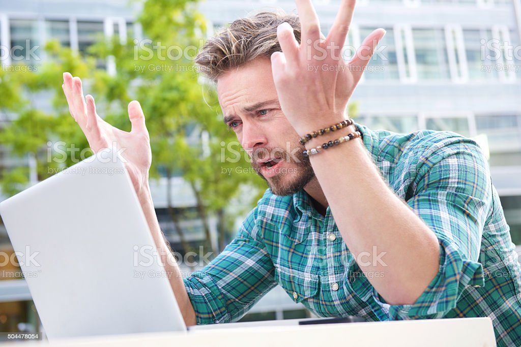 Stressed man looking at laptop with hands raised stock photo