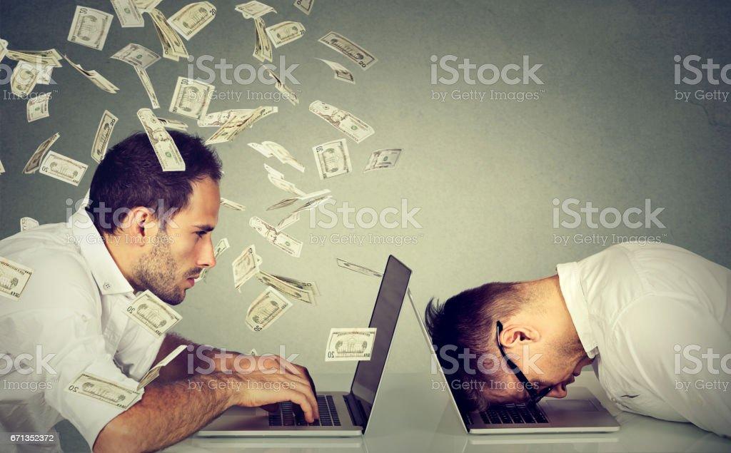 Stressed man resting on laptop next to professional under money rain stock photo