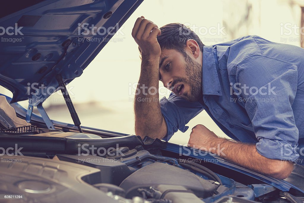 stressed man with broken car looking at failed engine stock photo