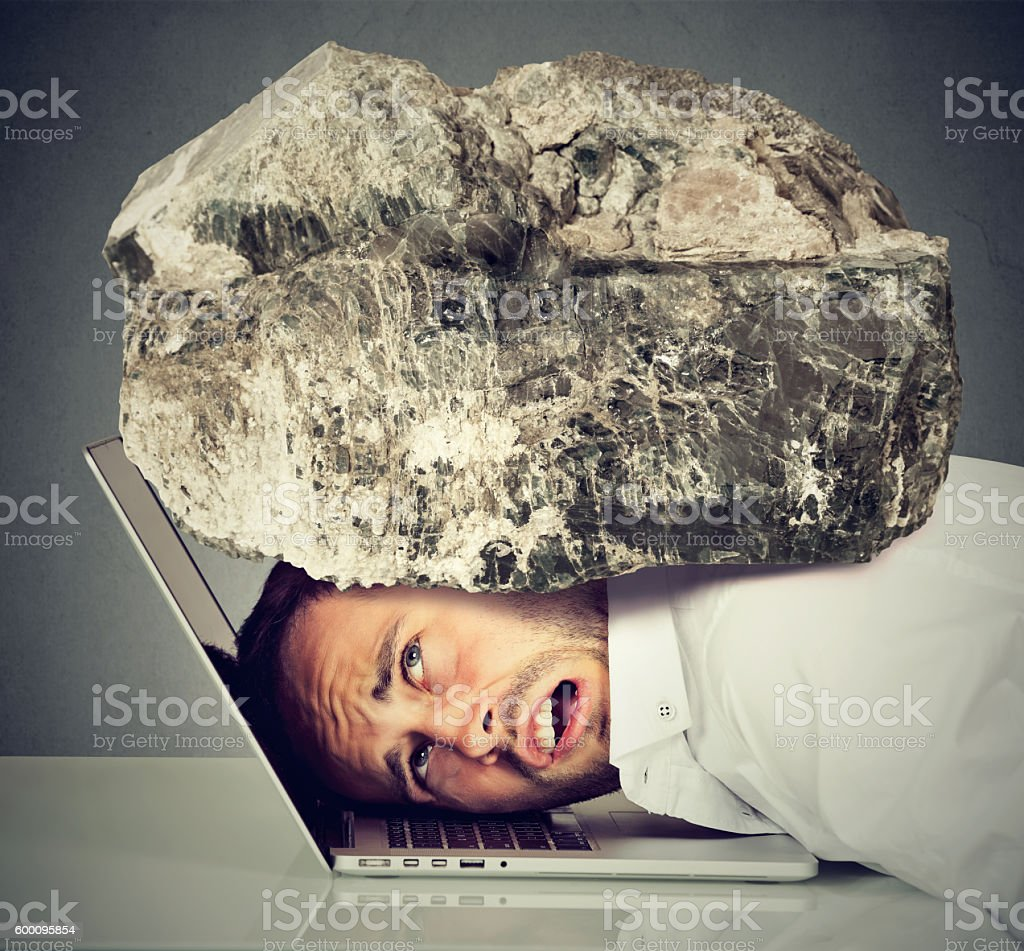 Stressed man with head squeezed between laptop and rock stock photo