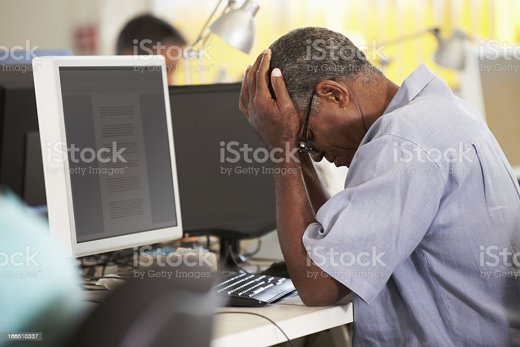 Stressed Man Working At Desk In Creative Office royalty-free stock photo