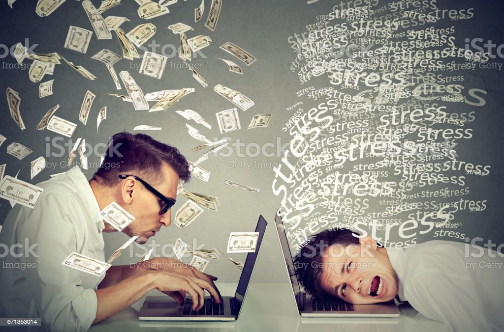 Stressed man working on laptop next to man under money rain. stock photo