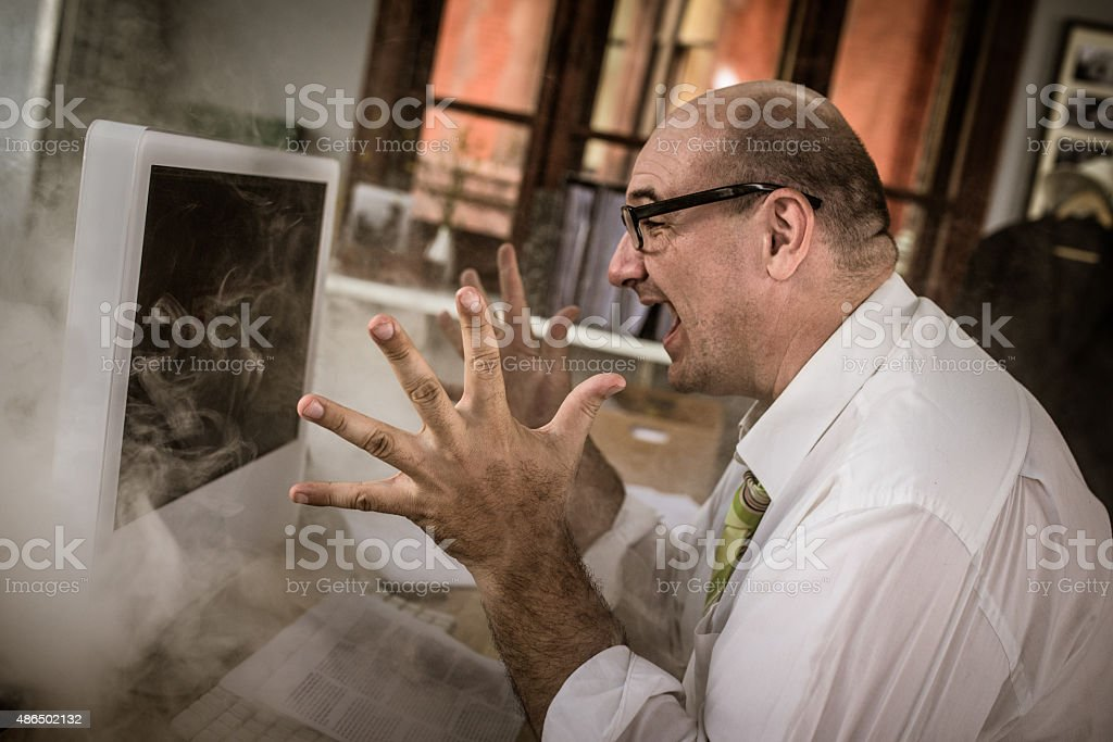 Stressed mature adult businessman using computer stock photo